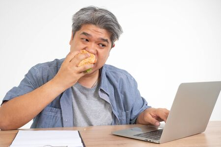 Asian man working and eating a burger on the office desk. Concept of a busy businessman cannot work-left balance and not taking care of health eat only junk food Stock Photo
