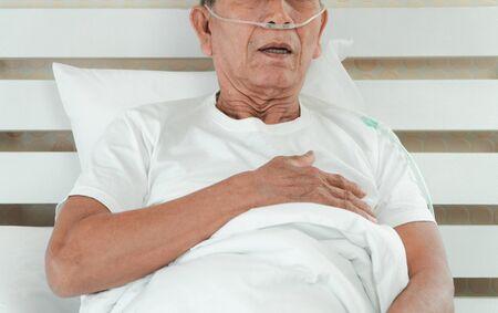 Triste homme âgé allongé sur le lit d'hôpital et avec un tube respiratoire nasal pour le traitement respiratoire. Concept de soins de santé pour les personnes âgées, coronavirus de quarantaine (COVID-19)