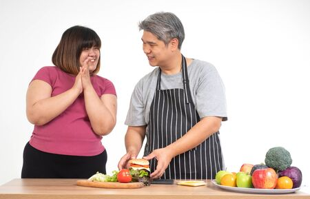Happy overweight couple cooking a burger in the kitchen room. A vegetable on the table. Concept of happy family and binge eating