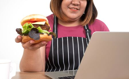 Hungry overweight woman smiling and holding a hamburger in the living room While work from home, her very happy and enjoy to eat fast food. Concept of binge eating disorder (BED).