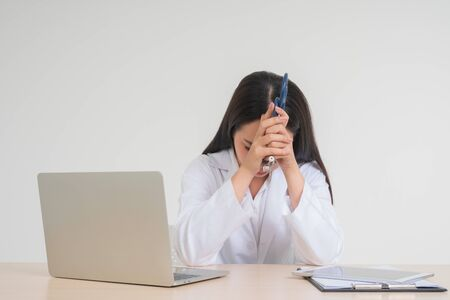 Young Asian woman doctor sitting on desk, she look unhappy and tired because of overwork, Concept of stressed exhausted and doctor liability, Dealing with frustrated
