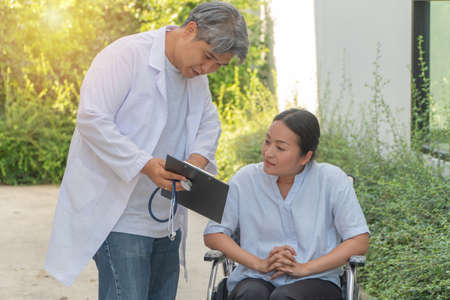 The doctor holds the clipboard and explained health problems And the effect of treatment for patients sitting in a wheelchair While walking in the garden. Concept of healthcare and medical service