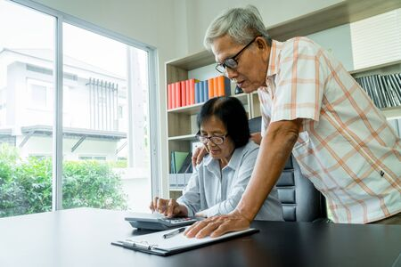 Senior Asian couple using the calculator and paperwork on desk at home to calculate expenses and income. And savings after retirement. Concept of financial planning and investment for retirees. Banque d'images