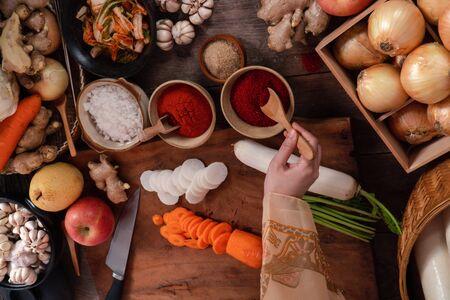 Asian women wearing Korean traditional costumes (hanbok) are mixing fresh stir-fry and kimchi ingredients with ingredients such as salt, garlic, gochugaru, fresh vegetables. Фото со стока