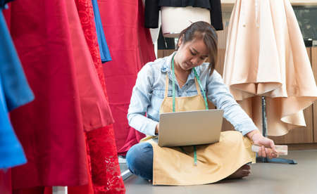 Stressed Asian entrepreneur sitting beside the window because her shop has stopped doing business. Due to financial problems And the economic slowdown. Concept of business crisis