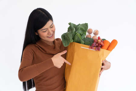 Happy Asian woman smiling and point the finger to a paper bag and carries a shopping bag after the courier from grocery came to deliver at home. Concept of Supermarket delivery for a new lifestyle.