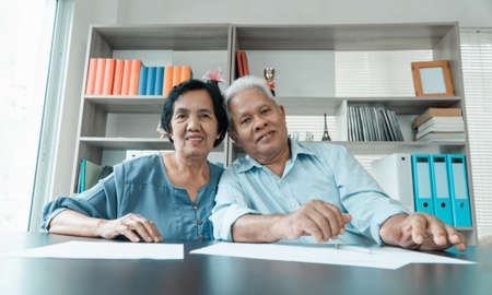 Senior Asian couple using the calculator and paperwork on desk at home to calculate expenses and income. And savings after retirement. Concept of financial planning and investment for retirees. Фото со стока