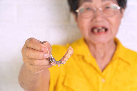 Asian Elderly woman over 70 years old holding dentures in hand. Dentures for prosthetic devices constructed to replace missing teeth and helping to chew food. The ability to chew food of the elderly