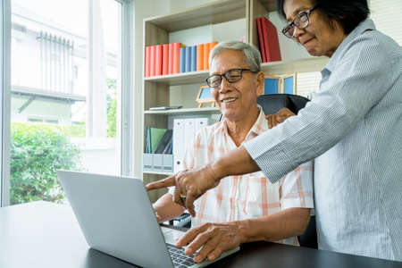 Happy senior Asian couple using a laptop at home for find new tourist attractions together. Happy retirement with planning, saving, pension And the good capital uncle of the elderly