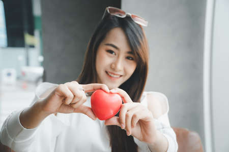 Portrait of beautiful happy Asian woman smiling and holding a red heart. Concept of love and relationship.