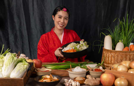 Asian women wearing Korean traditional costumes (hanbok) are mixing fresh stir-fry and kimchi ingredients with ingredients such as salt, garlic, gochugaru, fresh vegetables. Фото со стока