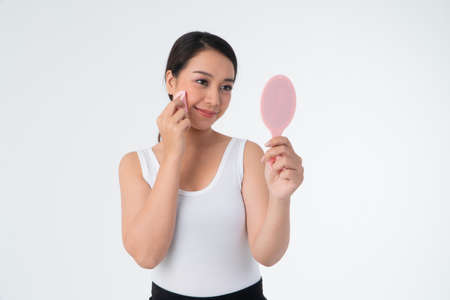 Beautiful young Asian woman cleaning her skin with a cotton pad and holding Makeup mirror,  isolated over white background