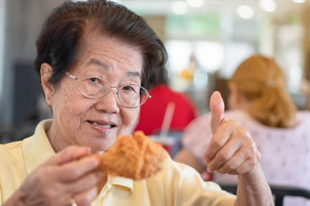 Asian elderly women are eating fried chicken. In the restaurant And lift the thumb. Her smile and look happy. Concept of aging society, Preparedness After retirement And living a happy life. Фото со стока