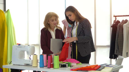 Elderly fashion designer is coach young women for how to design clothing and to be dressmaker stylist in a showroom. The Concept of study with professional and new entrepreneurs learn in the industry. Фото со стока