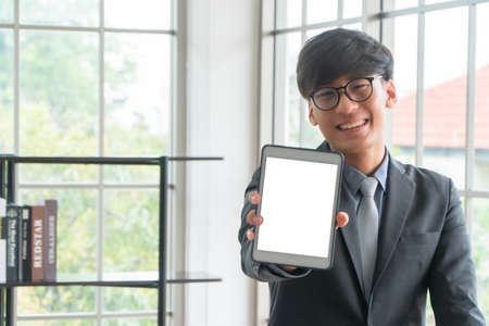 Young Asian businessman wearing a suit hold and showing front side view a white blank screen tablet mockup. Concept of professional introduce yourself, blank screen for text and content, advertisement