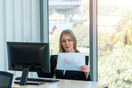 Serious caucasian businesswoman working at office desk, She looks tired bored and stressed. Concept of problems of new entrepreneurs are not able to successfully run a business