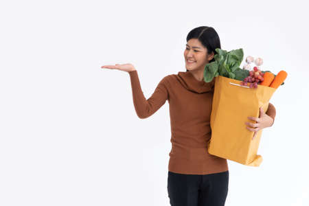 Happy Asian woman smiling and open the palm of the hand and carries a shopping bag after the courier from grocery came to deliver at home. Concept of Supermarket delivery for a new lifestyle.