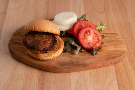 fresh tasty homemade hamburger with fresh vegetables, lettuce, tomato, cheese beside sliced tomatoes on a cutting board. Free space for text Фото со стока