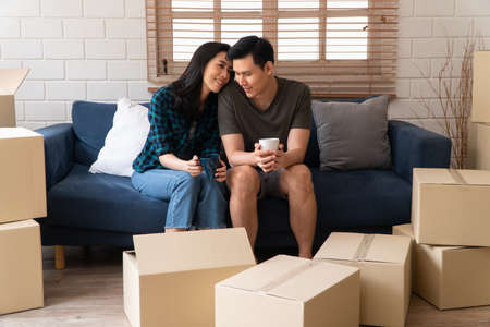 Happy young Asian couple holding a coffee cup and sitting on the sofa for rest after moving to a new house on the first day. Concept of starting a new life for a newly married couple.