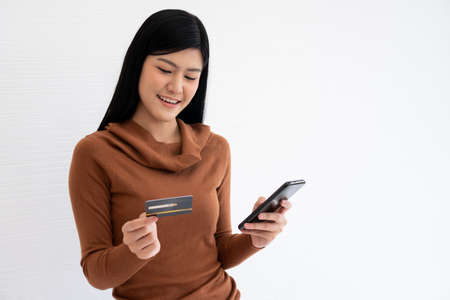 Happy Asian woman holding card credit and smartphone for mobile banking on the internet. Concept of new lifestyle and financing technology. Фото со стока