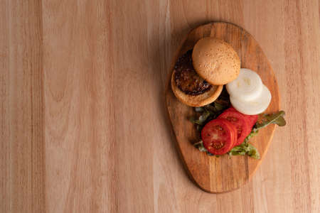Top view of fresh tasty homemade hamburger with fresh vegetables, lettuce, tomato, cheese beside sliced tomatoes on a cutting board. Free space for text Фото со стока