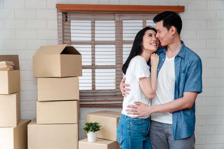 Smiling young Asian happy couple hugging boyfriend with cardboard boxes at moving day in their new home after buying real estate. Concept of starting a new life for a newly married couple. Фото со стока