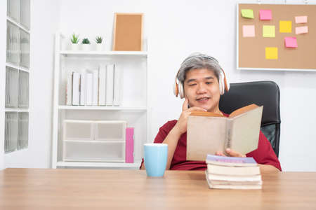 Relax elderly Asian man reading a book and listening to music in home office.