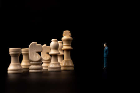 Figures businessman standing in front of wooden chess on black isolated background. Concept of business analysis and strategy. Stepping into the startup, new business player