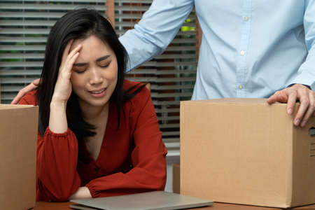 Sad Asian woman Packing belongings in a cardboard box and crying on the desk in the office After being layoff and unemployed. Concept of impact on the economic downturn And management of the failure