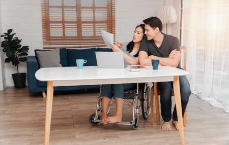 A woman in a wheelchair after a car accident and working with a computer at home with her lover. The concept of Mutual care and new technology has made people with disabilities Equality in society. Stock Photo