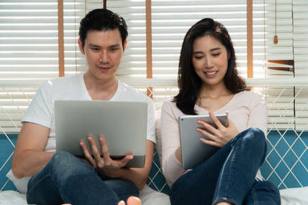 Happy young couple looking a tablet together for finding travel locations and book travel online for Honeymoon. Concept of Technology for convenience, Happiness after marriage