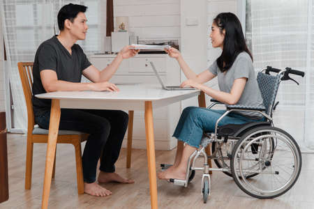 A woman in a wheelchair after a car accident and working with a computer at home with her lover. The concept of Mutual care and new technology has made people with disabilities Equality in society.