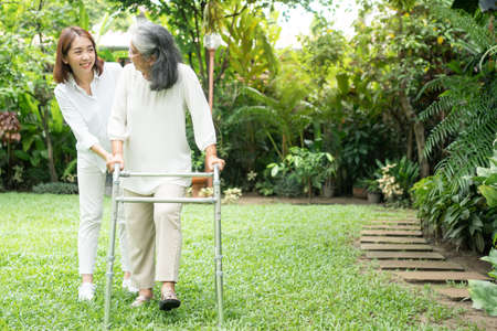 An old elderly Asian woman uses a walker and walking in the backyard with her daughter.  Concept of happy retirement With care from a caregiver and Savings and senior health insurance