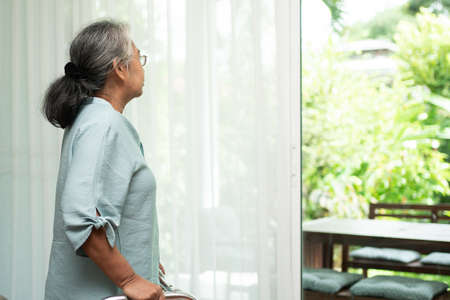 A sad old elderly woman uses Walker for standing in front of windows and looking outside and feeling lonely. Concept of depression caused by illness and Elderly caregivers 免版税图像