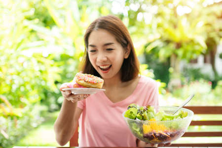 The happy beautiful Asian healthy middle aged woman sitting on the balcony beside the garden and choose between a donut and a vegetable salad. Concept of health care and nutritious food Reklamní fotografie