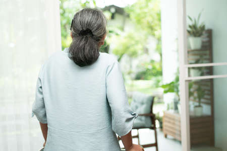 A sad old elderly woman uses Walker for standing in front of windows and looking outside and feeling lonely. Concept of depression caused by illness and Elderly caregivers Standard-Bild