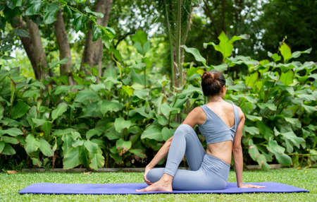 Portrait of a young woman doing yoga in the garden for a workout. Concept of lifestyle fitness and healthy. Asian women are practicing yoga in the park.