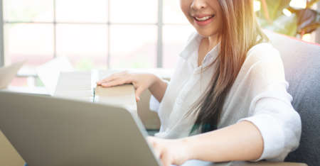 Happy young Asian woman entrepreneur, Smile for sales success after checking order from online shopping store in laptop at home office, Concept of merchant business online and eCommerce