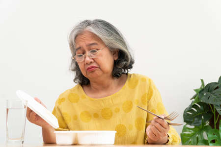 Unhappy Asian senior woman anorexia and say no to ready meals, Elderly home alone and bored food and no appetite