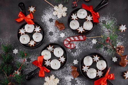Weihnachtsdekoration, zuckerpulverisierte Donuts mit Süßigkeiten in einer Mini-Eisenpfanne.