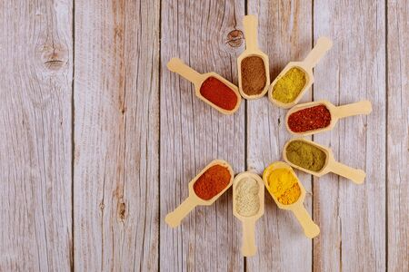 Assortment of spices in wooden spoons on white wooden background.