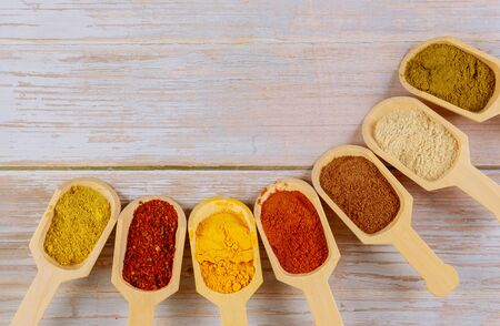 Assortment of colorful spices in the wooden spoons on wooden background.