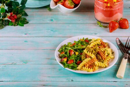 Tricolor rotini pasta from durum wheat with green salad on wooden blue table.