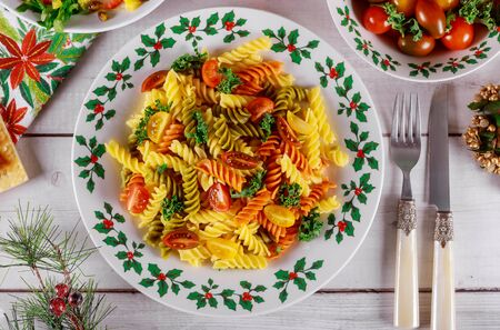Rotini pasta and cherry tomato with green salad on christmas table with knife and fork. Zdjęcie Seryjne