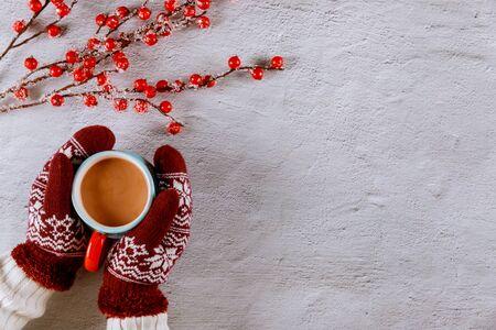 La mujer sostiene una taza de cacao caliente en guantes de punto.