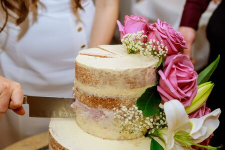 Groom and bride in white dress cut layer wedding cake, decorated with fresh pink roses and lily