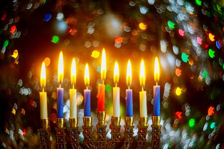 Menorah with burning candles for Hanukkah on sparkle background with defocused colorful lights. Jewish holiday. Archivio Fotografico