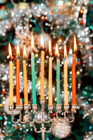 Menorah with burning candles for Hanukkah on sparkle background with defocused colorful lights. Jewish holiday.