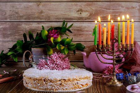 Hanukkah sweet pie with burning colored candles on menorah. Jewish holiday concept. Standard-Bild