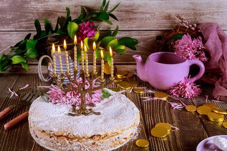 Menorah mit brennenden Kerzen auf festlichem Kuchen. Jüdischer Feiertag Chanukka.